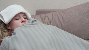 Un adolescente è coperto di coperta, la sua febbre, l'emicrania, influenza archivi video