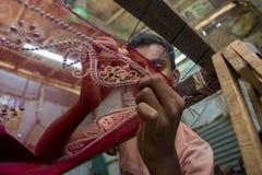 Un adolescente añade el detalle a una sari tradicional de Jamdani en Mirpur Benarashi Palli, Dacca, Bangladesh foto de archivo
