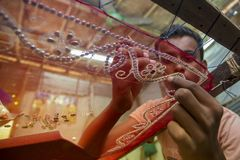 Un adolescente añade el detalle a una sari tradicional de Jamdani en Mirpur Benarashi Palli, Dacca, Bangladesh fotos de archivo