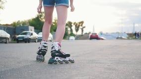 Un adolescente adentro patina sobre ruedas el patinaje en el camino - luz del día metrajes