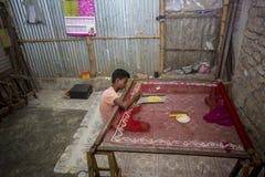 Un adolescente aggiunge il dettaglio ad un saree tradizionale di Jamdani in Mirpur Benarashi Palli, Dacca, Bangladesh fotografia stock libera da diritti