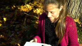 Un adolescente bonito joven se sienta debajo de un árbol en el bosque del otoño y lee un libro Ella sueña La muchacha es serena y almacen de video
