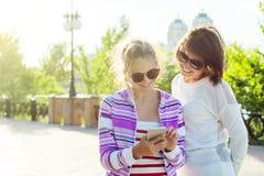 Un adolescente bonito y sus smartphones del uso de la madre, fotos de la visión, charla y sonrisa hermosos, en un día de verano s Fotos de archivo