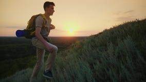 Un adolescente cansado sube a la montaña En la puesta del sol, lleva una mochila detrás de ella detrás metrajes