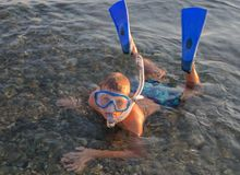 Un adolescente che indossa una maschera con il tubo per l'immersione e le alette Immagini Stock