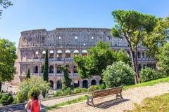 Un adolescente che riposa nel parco davanti al Colosseo a Roma fotografia stock