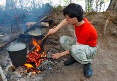 Un adolescente cocina la comida Fotos de archivo