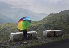 Un adolescente con el paraguas colorido Imagen de archivo libre de regalías