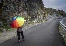 Un adolescente con el paraguas colorido Imagen de archivo