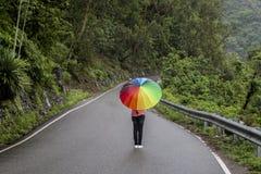 Un adolescente con el paraguas colorido Fotos de archivo