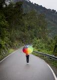Un adolescente con el paraguas colorido Fotos de archivo libres de regalías