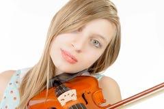 Un adolescente con el pelo largo toca el violín Foto de archivo
