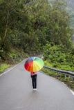 Un adolescente con l'ombrello variopinto Immagini Stock