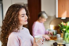 Un adolescente con la madre en la cocina en casa Foto de archivo libre de regalías
