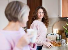 Un adolescente con la madre en la cocina en casa Fotos de archivo libres de regalías