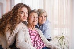 Un adolescente con la madre y la abuela en casa Fotos de archivo libres de regalías
