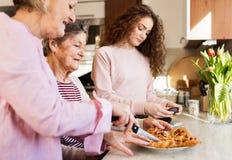 Un adolescente con la madre y la abuela en casa Imagen de archivo