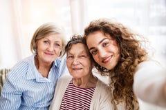 Un adolescente con la madre y la abuela en casa Fotografía de archivo