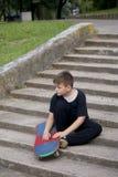 Un adolescente con un monopatín Se sienta con un monopatín contra el contexto de una escalera de piedra Imagen de archivo