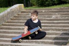 Un adolescente con un monopatín Se sienta con un monopatín contra el contexto de una escalera de piedra Foto de archivo