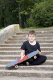 Un adolescente con un monopatín Se sienta con un monopatín contra el contexto de una escalera de piedra Imagen de archivo libre de regalías