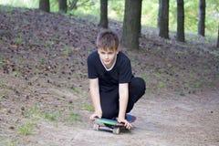 Un adolescente con un monopatín Se sienta en un monopatín Imagen de archivo