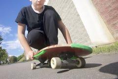 Un adolescente con un monopatín Se sienta en un monopatín Imagenes de archivo