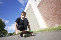 Un adolescente con un monopatín Se sienta en un monopatín Fotos de archivo libres de regalías