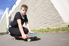Un adolescente con un monopatín Se sienta en un monopatín Foto de archivo
