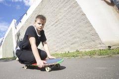 Un adolescente con un monopatín Se sienta en un monopatín Fotos de archivo