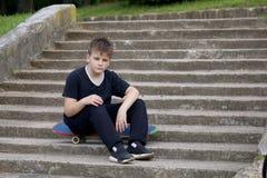 Un adolescente con un monopatín Se sienta en un monopatín contra el contexto de una escalera de piedra Imágenes de archivo libres de regalías