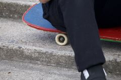 Un adolescente con un monopatín Se sienta en un monopatín contra el contexto de una escalera de piedra Fotografía de archivo libre de regalías