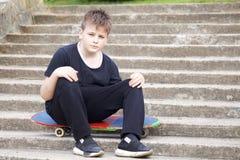 Un adolescente con un monopatín Se sienta en un monopatín contra el contexto de una escalera de piedra Imagenes de archivo