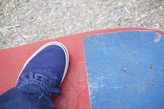 Un adolescente con un monopatín Se sienta en un monopatín Visión desde arriba Foto de archivo