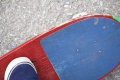 Un adolescente con un monopatín Se sienta en un monopatín Visión desde arriba Imagenes de archivo