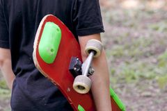 Un adolescente con un monopatín Sostiene un patín en las manos Fotos de archivo libres de regalías