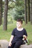 Un adolescente con un monopatín Sostiene un patín en las manos Imágenes de archivo libres de regalías