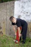 Un adolescente con un monopatín Sostiene un patín en las manos Imagen de archivo