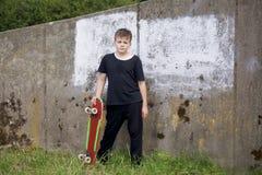 Un adolescente con un monopatín Sostiene un patín en las manos Imagen de archivo libre de regalías