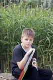 Un adolescente con un monopatín Sostiene un patín en las manos Fotos de archivo