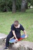 Un adolescente con un monopatín Sostiene un patín en las manos Foto de archivo libre de regalías