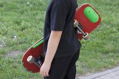 Un adolescente con un monopatín Sostiene un patín en las manos Fotografía de archivo