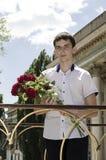 Un adolescente con un ramo de flores Imágenes de archivo libres de regalías