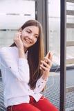 Un adolescente con un smartphone en sus manos pasa tiempo al aire libre Foto de archivo libre de regalías