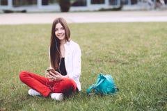 Un adolescente con un smartphone en sus manos pasa tiempo al aire libre Imagen de archivo libre de regalías