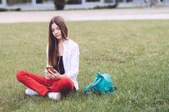 Un adolescente con un smartphone en sus manos pasa tiempo al aire libre Imágenes de archivo libres de regalías