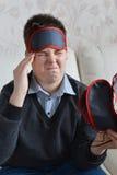 Un adolescente con un dolor de cabeza en la máscara para el sueño Imagenes de archivo