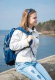 Un adolescente con una mochila delante del mar Imagen de archivo
