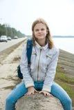 Un adolescente con una mochila delante del mar Imagenes de archivo