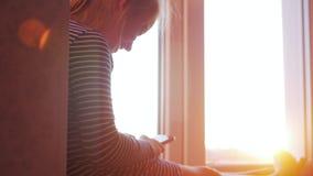 Un adolescente de la niña que se imagina historia con el libro en la ventana abierta en travesaño en fondo de la puesta del sol L metrajes
